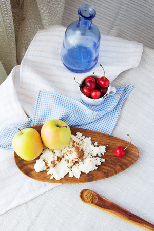reason: Composition of fruits and berries, cottage cheese. Reason for the longevity is apples, cherries. Fruits and berries, cottage cheese in a bowl on a checkered napkin on the table.