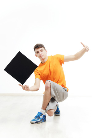 rapping: Young man with sign he is holding against a white background. Young rapper is holding a sign. Dancer is wearing in orange T-shirts with sign in a hand. Hip-hop dancer advertise something Stock Photo