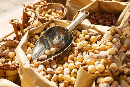 Roasted hazelnut in paper envelope food festival. Background, pattern of hazelnut. Nuts on street food festival, fair. Protein.