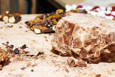 Homemade healthy vegan chocolate. Crushing chocolate on a chopping board. Chunk of dark chocolate close up with crumbs.