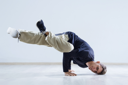 agressive: Hip hop dancer performing isolated over white background. Hip hop performer is standing on the hand.