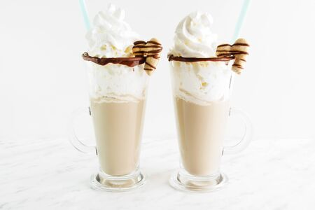 Sweet cocktail with milk, cocoa, syrup, cream, decorated with cookie in the shape of a heart. Saint valentines day. Heart Shape Cookie On Edge. Stock Photo