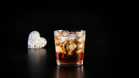 Hearts and a glass of alcohol on a black table in the bar. Lonely scottish glass of whiskey with ice on Valentines Day. Stock Photo