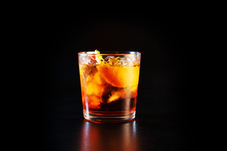 Glass of alcohol on a black table in the bar. Lonely scottish glass of whiskey with ice. Stock Photo
