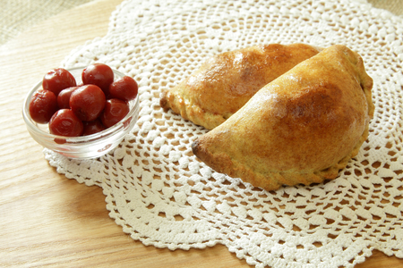 Russian pirozhki, baked patties or pies on basket with cherry Stock Photo
