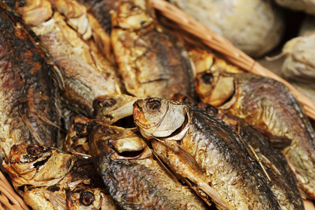 Dried, smoked, small fish used in Asian cuisine. Cooked sprat fish background or pattern. Delicatessen dried, smoked, sprat fish for beer on street food festival. Standard-Bild