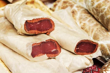 Rundvlees. Gedroogde rundvlees rundvlees ruwachtig op de achtergrond van de snijplank. Droogvlees, rustieke landstijl. Heerlijk vlees eten.