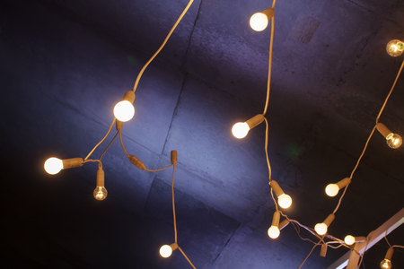 Decorative garland lights on the concrete background