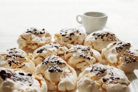 Sluit omhoog van schuimgebakjes met kop van koffie op witte houten lijst als voedselachtergrond. Bovenaanzicht.