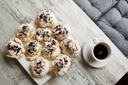Close up of meringues with cup of coffee on white wooden table as food background. Top view.