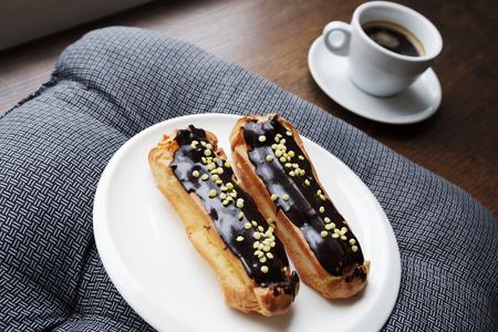 Witte plaat met koffie eclairs met kopje verse zwarte koffie op grijs textiel servet over houten tafel. Bovenaanzicht