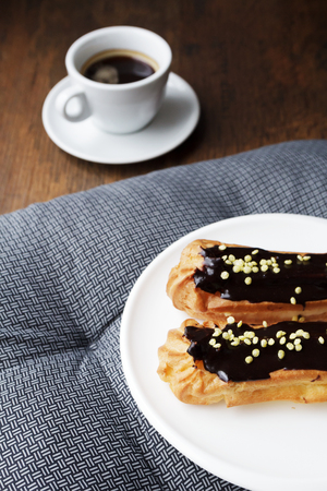 White plate with Coffee eclairs with cup of fresh black coffee on gray textile napkin over wooden table. Top view.