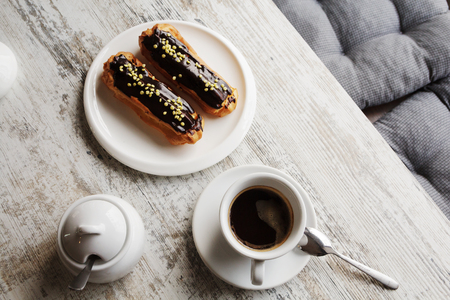 White plate with Coffee eclairs with cup of fresh black coffee on wooden table. Top view.