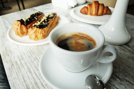 Witte plaat met koffie eclairs en croissant met kopje verse zwarte koffie op houten tafel. Bovenaanzicht. Stockfoto