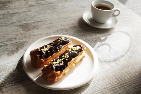 Witte plaat met koffie eclairs met kopje verse zwarte koffie op houten tafel. Bovenaanzicht.