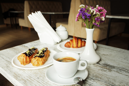 White plate with Coffee eclairs and croissant with cup of fresh black coffee on wooden table. Top view.