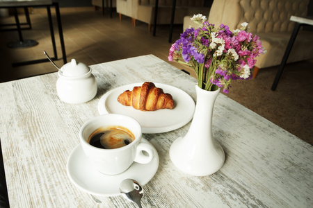 Witte plaat met croissant met kopje verse zwarte koffie op houten tafel. Bovenaanzicht Stockfoto