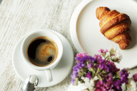 Witte plaat met croissant met kop verse zwarte koffie op houten tafel. Bovenaanzicht