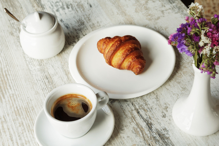 White plate with croissant with cup of fresh black coffee on wooden table. Top view. Standard-Bild