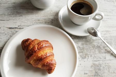 Witte plaat met croissant met kop verse zwarte koffie op houten tafel. Bovenaanzicht Stockfoto - 88540204