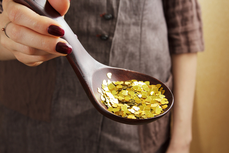 Wooden spoon full of decorational golden sequins in womans hand