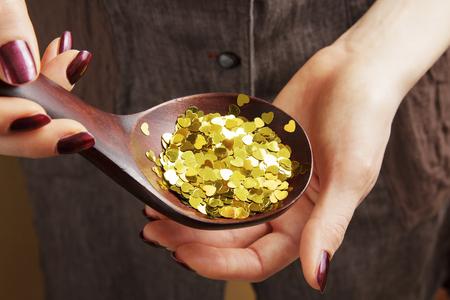 Houten lepel vol decoratieve gouden pailletten in de hand van de vrouw Stockfoto - 97764425