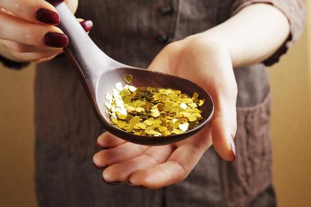 Houten lepel vol decoratieve gouden pailletten in de hand van de vrouw Stockfoto - 97733768
