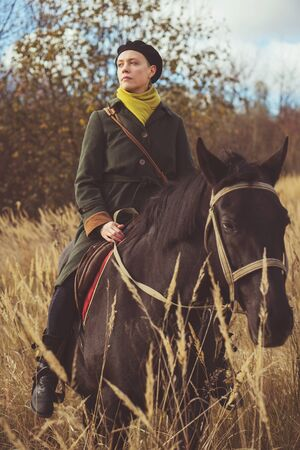 Young pretty girl riding a horse wearing a retro coat in the forest Stockfoto
