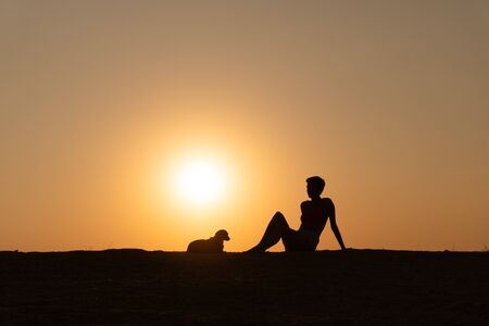 a silhouette of a woman is sitting on the beach with her little dog at sunset