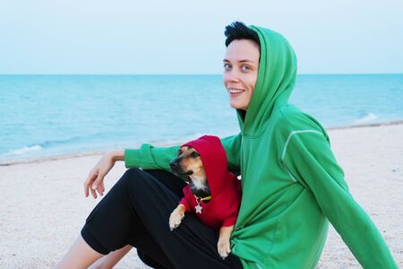 Young woman and dog near the sea dressed in the same clothes Stockfoto