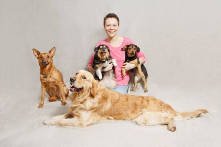 young woman in pink sweater with four dogs in studio