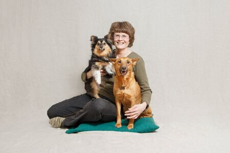 senior woman with two dogs in studio