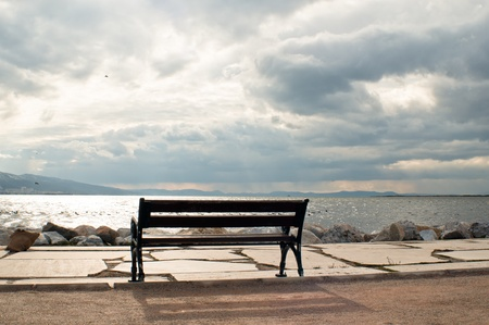 Empty low stool at the coast of the cloudy blue sea photo