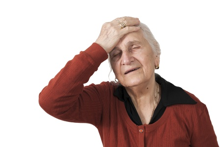 Old woman has migraine head ache sickness holding her head on white background Imagens