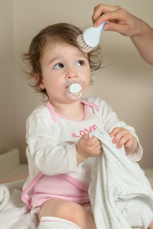 daugther: Mother combing her baby girl Stock Photo