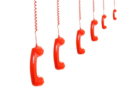 Isolated dangling red retro telephone receivers over white photo