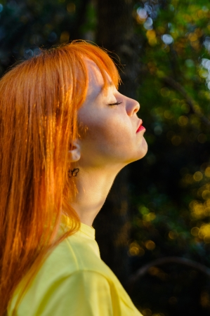 Red haired young girl taking a deep breath against sun