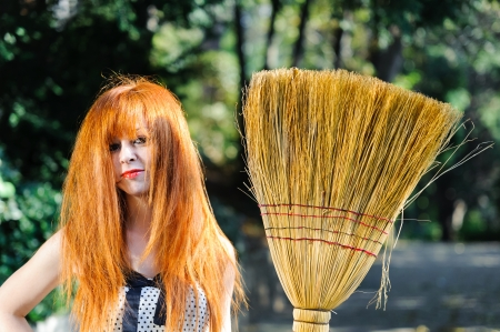 untidy: Untidy red haired cute young girl with broom