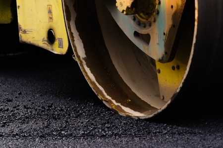 flatten:  Compact steamroller flatten out the asphalt tar