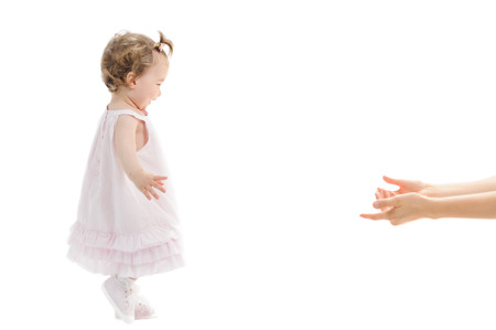 the first step: Isolated first steps of cute baby girl to her mothers arms Stock Photo