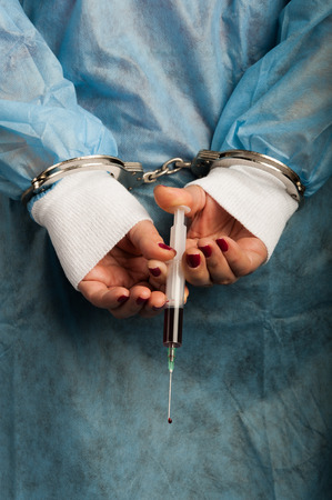 손에 피 묻은 주사기와 형사 수갑 의료 사람 스톡 콘텐츠 - 25969674