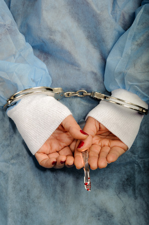 swindling: Criminal handcuffed medical person with bloody lancet in hand Stock Photo