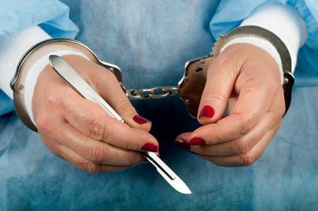 cuffed: Criminal handcuffed medical person with lancet scalpel in hand Stock Photo