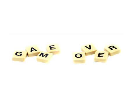 Isolated game over bankruptcy scrabble text on white background photo