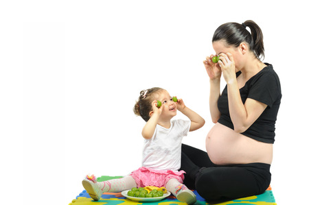 Isolated first child playing to her pregnant mother with fruits Imagens