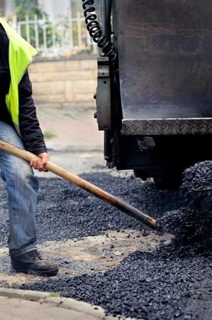 Worker manually effusing the asphalt with paving machine photo