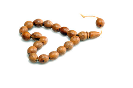 catholicism: Isolated made of teak tree rosary on white background Stock Photo