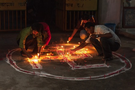 CHITWAN, NEPAL - OCTOBER 27, 2014: People lightning candles on Swastika symbol Buddhist tradition.The symbol can be commonly found in Buddhist temples religious artifacts founded by religious groups