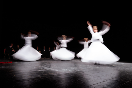 ceremonial clothing: ISTANBUL, TURKEY - FEBRUARY 02, 2012: Whirling mevlevi dervis in worship show Galata Istanbul. They are also known as the Whirling Dervishes due to their famous practice of whirling as form of dhikr.