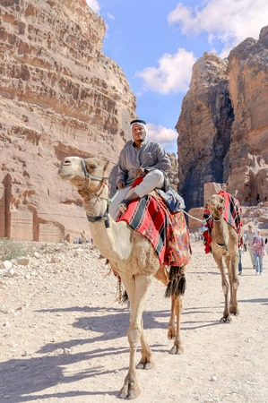 lessee: WADI MUSA, JORDAN - NOVEMBER 18, 2012:  Camels for rent and arab lessee at path in ancient Petra city. Petra is historical and archaeological city and famous for its rock-cut architecture and water conduit system. Another name for Petra is the Rose City d Editorial